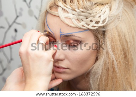 Closeup portrait of a woman having applied makeup by makeup artist