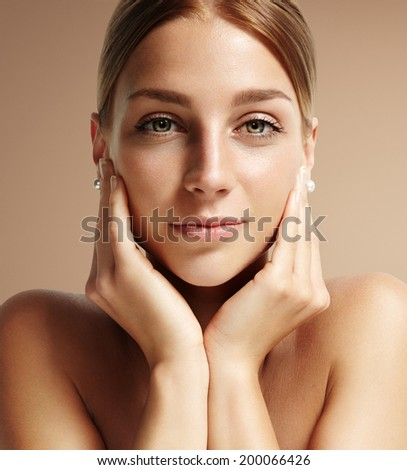 closeup portrait of a woman looking straight at camera and touching her face - stock photo