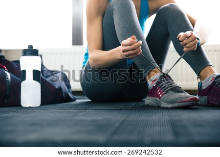 Closeup portrait of a woman tying shoelaces - stock photo