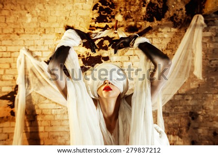 Closeup portrait of a woman with closed by bandage face and red lips stretching hands up at bricks wall background. - stock photo