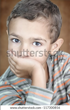 Closeup portrait of a 5 year old child looking at the camera and covering his mouth - stock photo