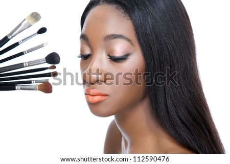 Closeup portrait of a young African beauty and make up brushes - stock photo