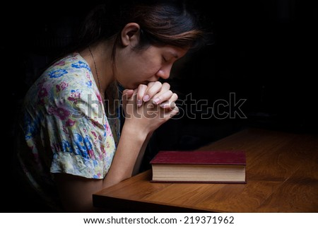 Closeup portrait of a young asian woman praying - stock photo
