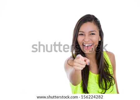 Closeup portrait of a young, beautiful, excited, happy woman smiling and pointing finger towards you and to the camera, isolated over white background with copy space - stock photo