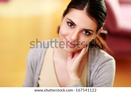 Closeup portrait of a young beautiful smiling woman at home - stock photo