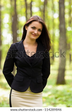 Closeup portrait of a young businesswoman standing in the woods - stock photo