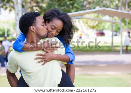 Closeup portrait of a young couple, guy giving woman piggy back ride and kissing face, happy moments, positive human emotions on isolated outdoors outside park background.  - stock photo