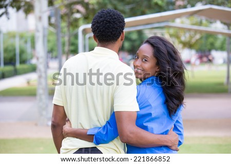 Closeup portrait of a young couple holding, embracing each other, expression of love, happy moments, positive human emotions on isolated outdoors park background. Women in blue shirt looking back - stock photo