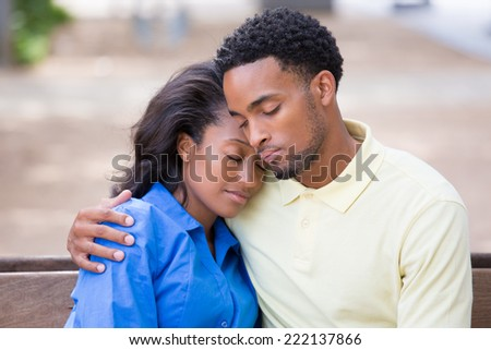 Closeup portrait of a young couple holding, embracing each other, eyes closed sleeping, expression of love, happy moments, positive human emotions on isolated outdoors park bench background.  - stock photo