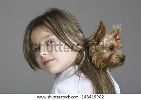 Closeup portrait of a young girl holding dog against gray background - stock photo