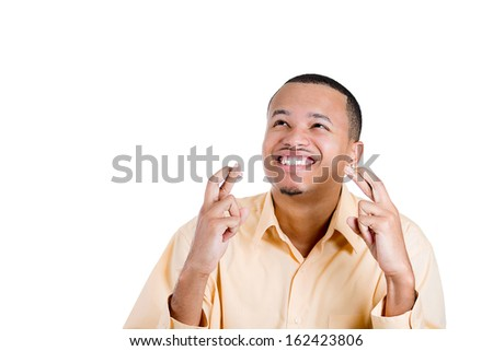 Closeup portrait of a young handsome man crossing fingers wishing and praying for miracle, hoping for the best, isolated on white background with copy space. Human emotions and facial expressions. - stock photo