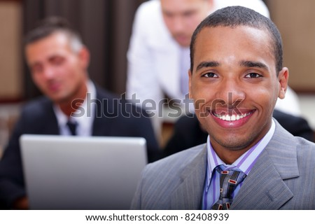 Closeup portrait of a young happy african businessman with colleagues on the background - stock photo