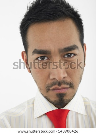 Closeup portrait of a young man frowning against white background - stock photo