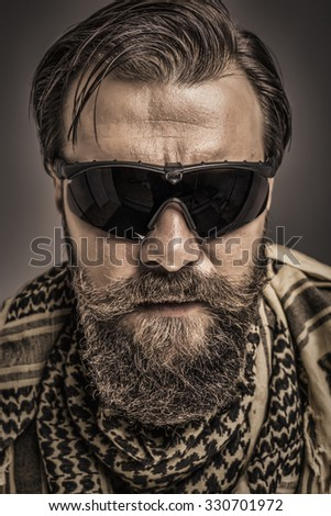 Closeup portrait of a young man with beard wearing a traditional arabic scarf and black glasses over gray background - stock photo