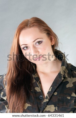 Closeup portrait of a young pretty female model in military outfit in studio - stock photo