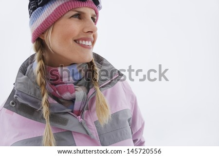 Closeup portrait of a young smiling woman in winter clothing - stock photo