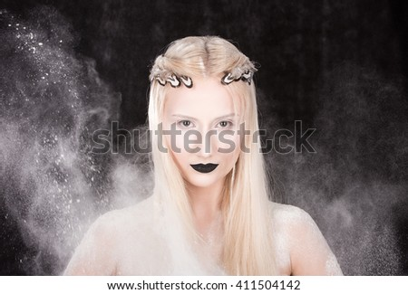 Closeup portrait of a young woman in a white cloud on a black background. Hairstyle with feathers in hair and makeup. Bleached skin and black lipstick - stock photo