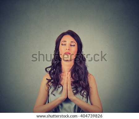 Closeup portrait of a young woman praying eyes closed isolated on gray wall background  - stock photo