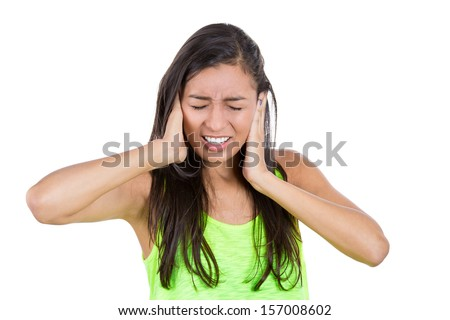 Closeup portrait of a young woman suffering from a migraine headache on top of a loud noise coming from a neighbor, holding hands to ears covering to shut out noise, isolated on white background.  - stock photo