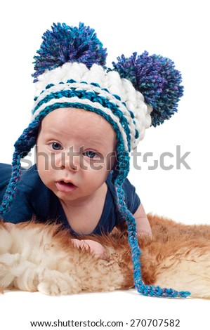 Closeup portrait of adorable baby boy in hat with pom-pom lying on fur - stock photo