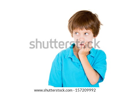 Closeup portrait of adorable boy in blue shirt looking sideways while biting fingernails because of craving for something or anxiety isolated on white background with copy space - stock photo