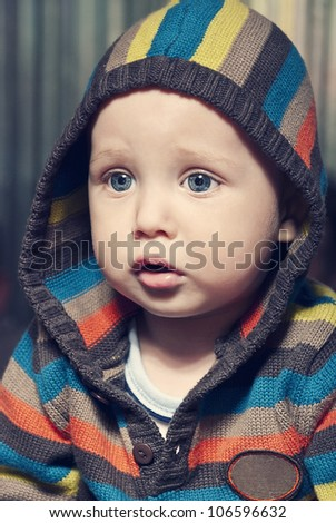Closeup portrait of adorable child in hood. - stock photo