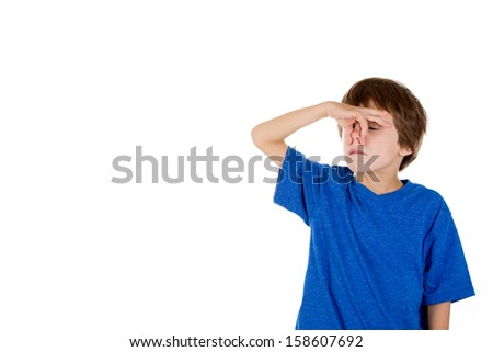 Closeup portrait of adorable kid pinching nose together because something stinks, isolated on white background with copy space - stock photo