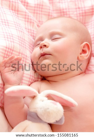 Closeup portrait of adorable newborn baby asleep, child care, closed eyes, toddler dreaming with plush toy, cute infant sleeping at home