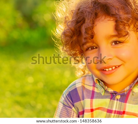 Closeup portrait of adorable sweet child on summer field, nice little boy with curly hair having fun on backyard, happiness and joy concept  - stock photo