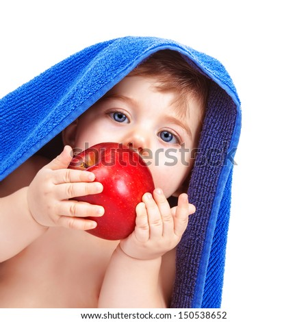 Closeup portrait of adorable toddler wrapped in blue towel, isolated on white background, baby boy biting red apple, infant after bath, healthy kids food  - stock photo