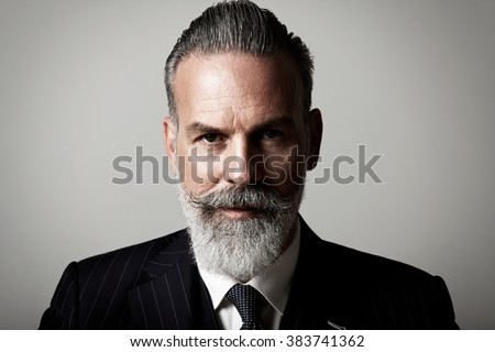 Closeup portrait of adult businessman wearing trendy suit  against the empty wall. Horizontal - stock photo
