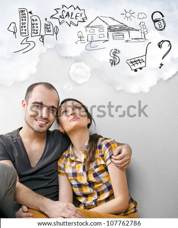 Closeup portrait of adult couple sitting on floor at their apartment and planning renovation of their new apartment while resting during housework - stock photo