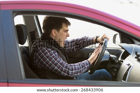 Closeup portrait of aggressive male driver honking in traffic jam - stock photo
