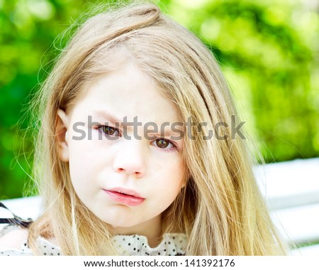 Closeup portrait of an adorable blond crying little girl with tears on her cheeks - stock photo