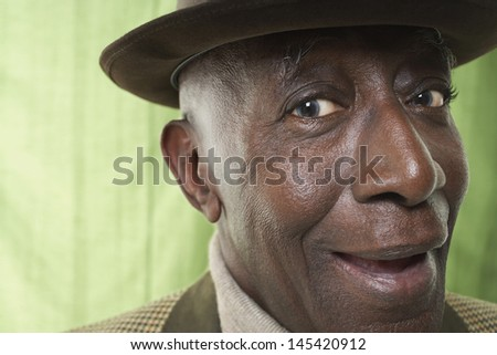Closeup portrait of an African American senior man wearing a hat against green curtain - stock photo