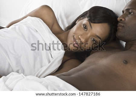 Closeup portrait of an African American woman with man in bed - stock photo