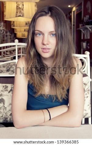 Closeup portrait of an amazing fresh young woman sitting at the cafe with hands crossed in blue dress with blue eyes looking awesome