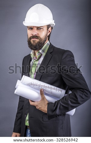 Closeup portrait of an angry engineer holding blueprint over gray background - stock photo