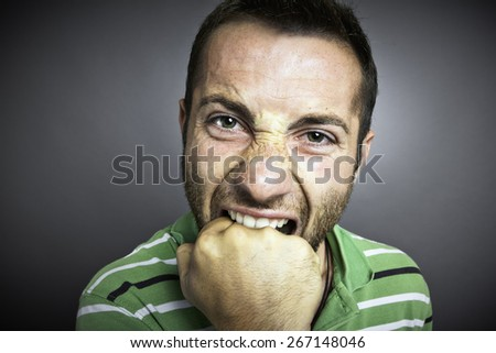 Closeup portrait of an angry guy biting his fist, looking at the camera. - stock photo