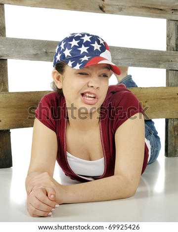 Closeup portrait of an attractive teen with a red, white and blue stars-and-stripes hat.  And wearing a silly expression on her face.