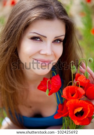 Closeup portrait of an attractive woman in a poppy field with flowers