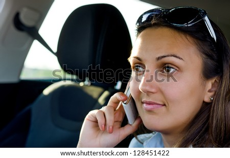 Closeup portrait of an attractive woman with her sunglasses pushed up on her forehead using her mobile phone in a car - stock photo