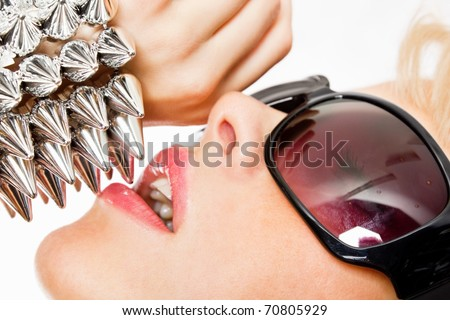 Closeup portrait of an attractive young fashionable girl wearing sunglasses and spike bracelet - stock photo