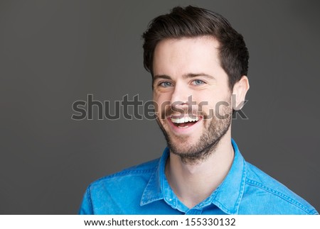 Closeup portrait of an attractive young man laughing on gray background - stock photo