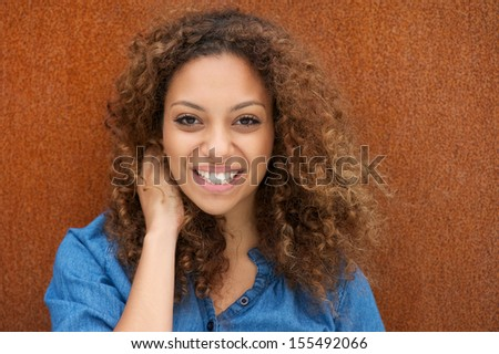 Closeup portrait of an attractive young woman smiling with hand in hair - stock photo