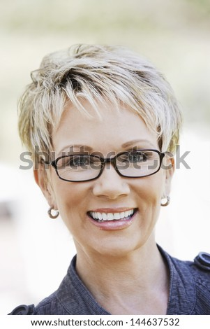 Closeup portrait of an elegant middle aged woman wearing glasses - stock photo