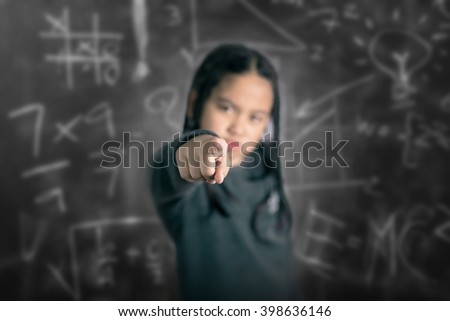 Closeup portrait of Angry Cute little asian girl pointing with her finger - stock photo