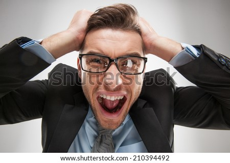 Closeup portrait of angry, frustrated man, pulling his hair out. Negative human emotions and facial expressions - stock photo