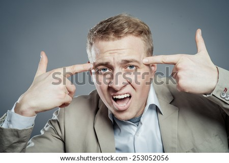 Closeup portrait of angry man gesturing with his finger against his temple, are you crazy? - stock photo