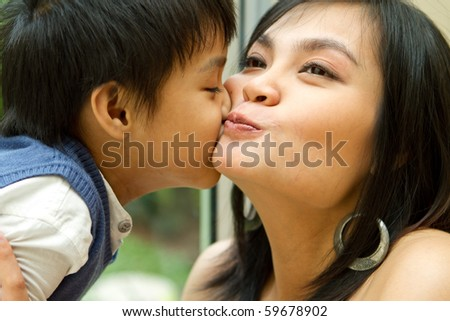Closeup portrait of asian ethnic boy kiss his happy mother - stock photo